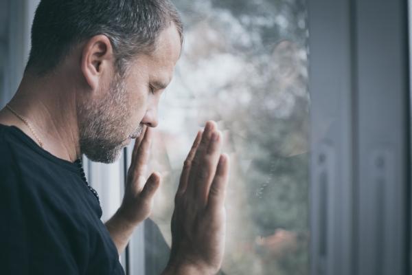 hombre con agorafobia mirando por la ventana
