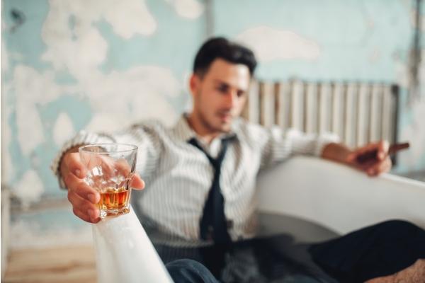 hombre con una crisis de ansiedad fumando y bebiendo